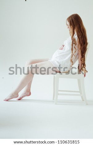 Beautiful young pregnant woman is sitting - stock photo