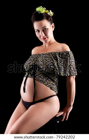 Beautiful young pregnant woman, isolated on black - stock photo