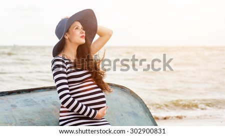 Beautiful young pregnant woman on the beach feels peace and tranquility - stock photo