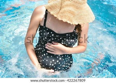 Beautiful young pregnant woman sitting and swimming in the jacuzzi swimming pool outdoors - stock photo