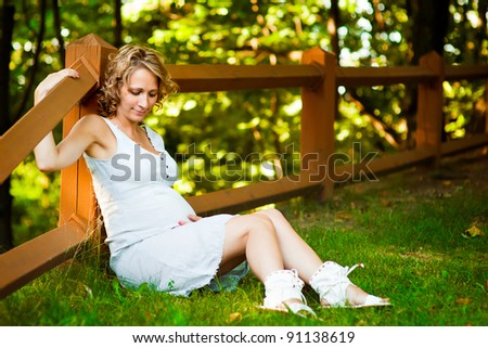Beautiful young pregnant woman sitting on gragg and holding bell - stock photo