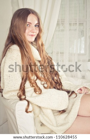 Beautiful young pregnant woman sitting on sofa - stock photo