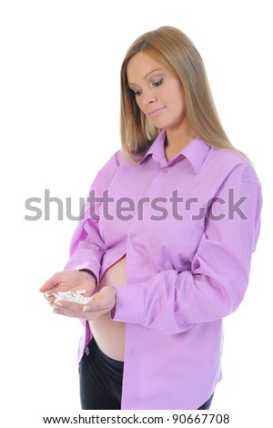 beautiful young pregnant woman with pills in hand. Isolated on white background - stock photo