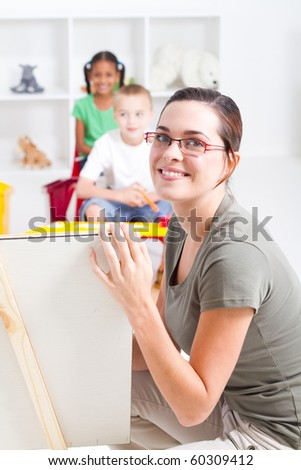 beautiful young preschool teacher teaching in classroom - stock photo