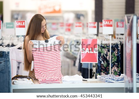Beautiful young pretty woman in shopping centre store choosing clothes looking at trendy striped red and white dress at summertime sale. Sale in shopping mall concept. Red sale signs on background - stock photo