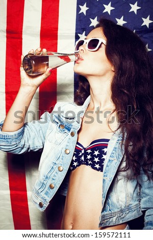 Beautiful young pretty woman in sunglasses with national usa flag in background drinking water. Lifestyle - stock photo