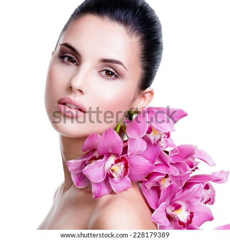 Beautiful young pretty woman with healthy skin and flowers close to face - isolated on white. - stock photo