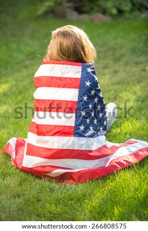 Beautiful young pretty woman with national usa flag over green natural background, focus on flag - stock photo