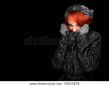 beautiful young red hair woman wearing a warm winter hat and coat, black background - stock photo