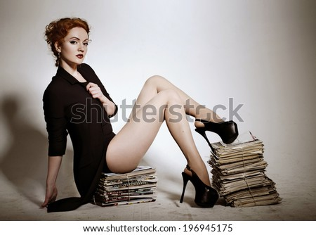 Beautiful young red haired business woman in a jacket barelegged sitting on newspapers studying news in white background. Journalism. Stylish conceptual photo.