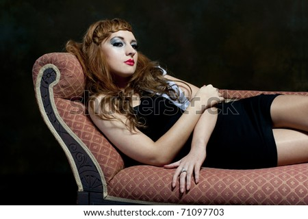 Beautiful young red haired female relaxing on chaise