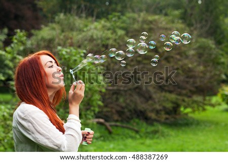 Beautiful young red-haired woman and bubbles on outdoors