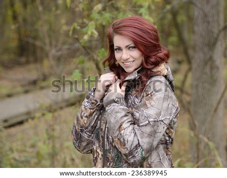 beautiful young red haired woman in camouflage attire in woods - hunting series - stock photo
