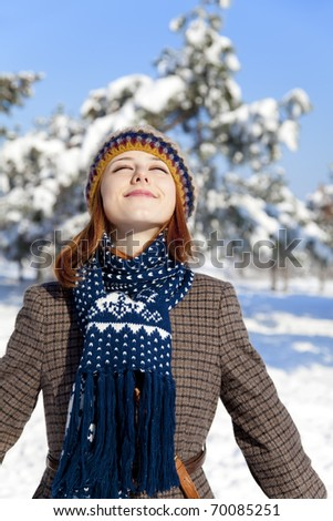 Beautiful young red-haired woman in winter park - stock photo