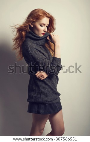 Beautiful young red haired woman with nice make up in autumn color, red lips, turtleneck. Fashion studio photo - stock photo