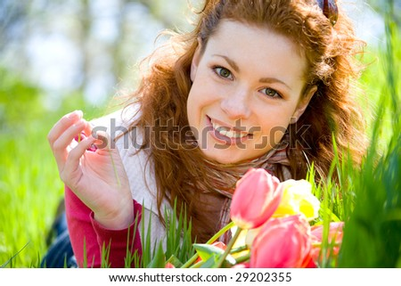 Beautiful young red-haired woman with red tulips on green meadow