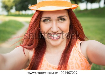 Beautiful young redhead Caucasian woman taking a selfie. Cute young teenage girl with ginger hair, orange shirt and hat taking a self portrait outdoors in park on sunny summer day. - stock photo