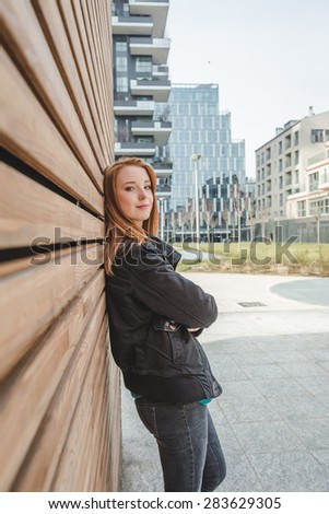 Beautiful young redhead girl posing in the city streets