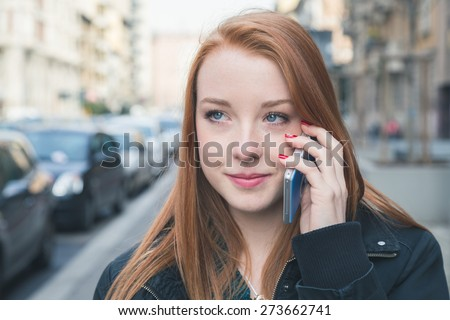 Beautiful young redhead girl talking on phone in the city streets - stock photo