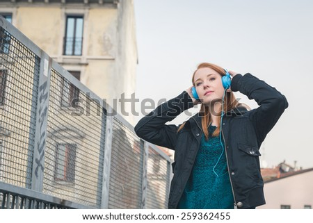 Beautiful young redhead girl with headphones listening to music in the city streets - stock photo