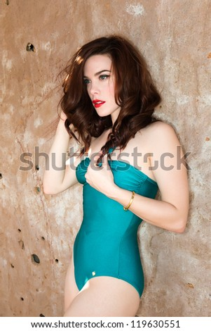 Beautiful young redhead in a teal swimsuit - stock photo