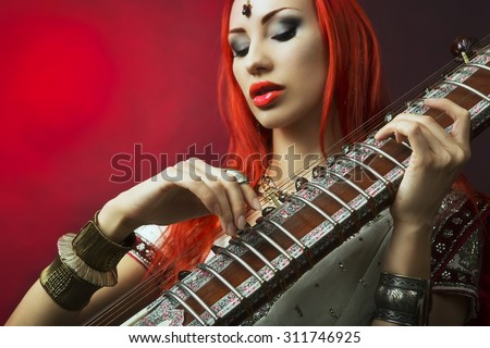 Beautiful Young Redhead Sexy Woman in Traditional Indian Sari Clothing with Oriental Jewelry and Bridal Makeup Playing Raga the Sitar. Beautiful hot Bollywood Girl. Eastern Music  - stock photo