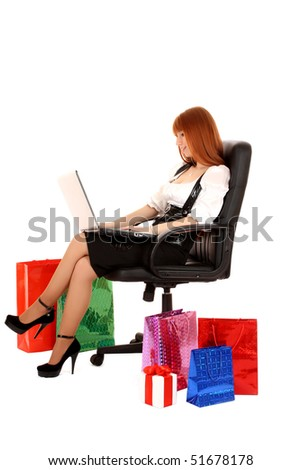 Beautiful, young, redhead woman with color shopping bags shopping over internet. On white background. - stock photo