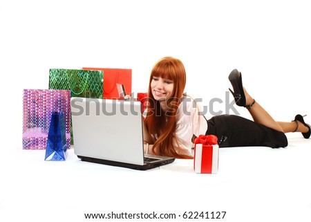 Beautiful, young, redhead woman with color shopping bags shopping over internet. On white background - stock photo