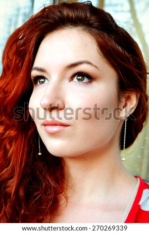 Beautiful young redhead woman with perfect daytime makeup and long silver earrings smiling playfully - stock photo