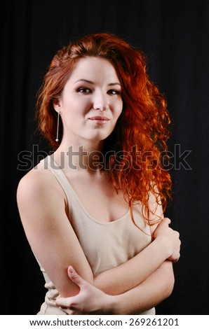 Beautiful young redhead woman with perfect daytime makeup smiling playfully - stock photo