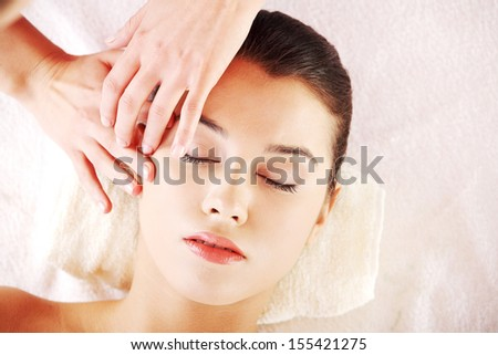 Beautiful young relaxed woman enjoy receiving face massage at spa  - stock photo