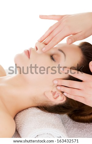Beautiful young relaxed woman enjoy receiving face massage at spa saloon. Isolated on white.