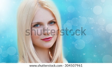 Beautiful young romantic elegant woman face, has blue eyes, blonde nature hair. Winter blue background. Pure makeup. Frozen snowflakes sky. Christmas holiday. - stock photo