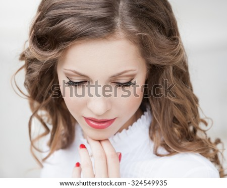 Beautiful young romantic elegant woman face, has closed eyes, haired nature hair, long eyelashes, hand with red manicure, sexy lips. Pure makeup. White blouse.  Nature dye - stock photo