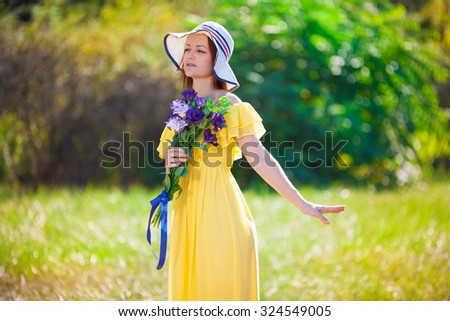 Beautiful young romantic elegant woman, has happy fun cheerful smiling face, yellow dress, flowers, white hat. Pure makeup. Nature background. Sunny day.  - stock photo