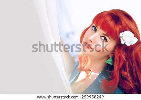 Beautiful young romantic tender red hair woman with white rose in her hair looking at camera on bright blur background with copy space - stock photo