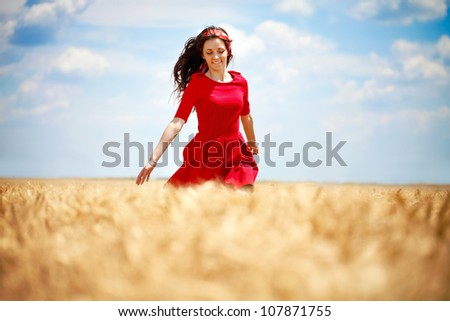 beautiful young, romantic woman running across wheat field