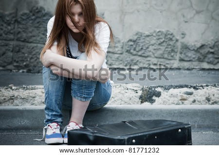Beautiful young sad girl sitting on asphalt. Photo in cold faded tones - stock photo