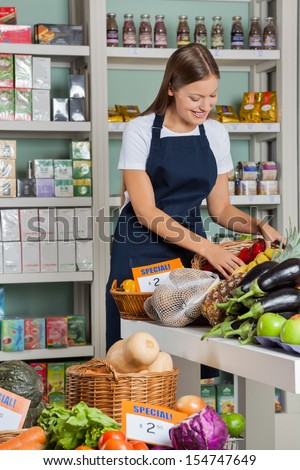 Beautiful young saleswoman working in supermarket - stock photo