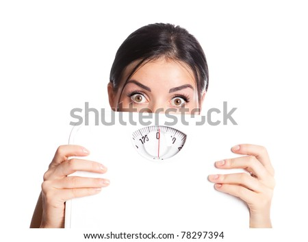 beautiful young scared  woman  holding scales, isolated against white background