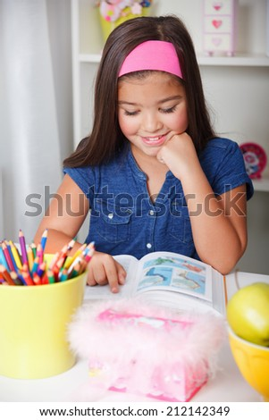 Beautiful young school girl reading a book