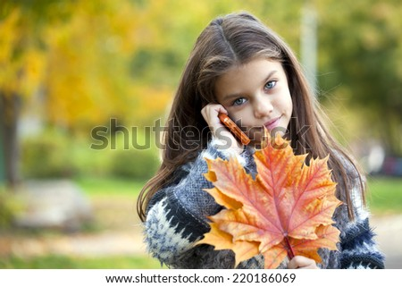 Beautiful young school girl talking on mobile phone in the autumn park - stock photo