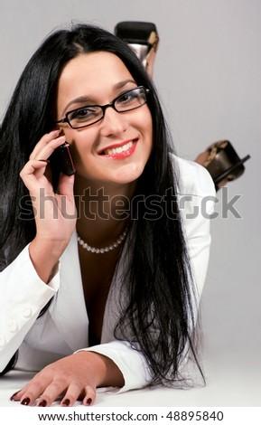 Beautiful young secretary is having phone conversation - stock photo