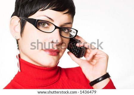 Beautiful young secretary with charming big green eyes is bearing modern glasses and receiving calls on a mobile phone. - stock photo