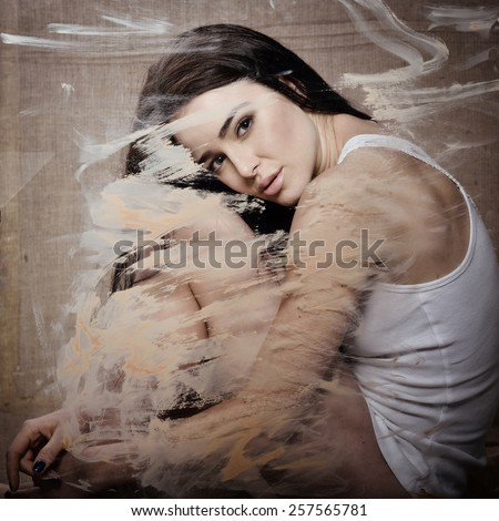 Beautiful young sensual woman on canvas behind painted window glass, image toned. - stock photo