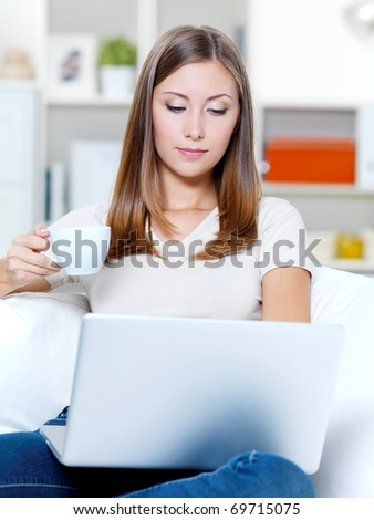 Beautiful young serious woman with laptop and cup of coffee on the sofa