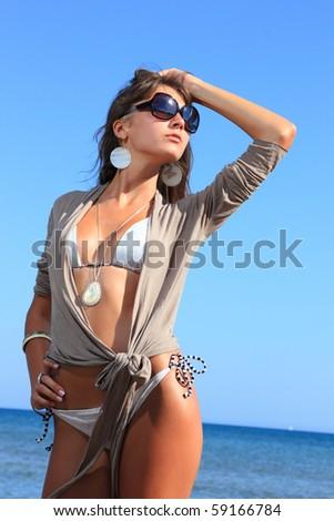 Beautiful young sexy bikini model by the sea - stock photo