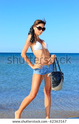 Beautiful young sexy bikini model by the sea - stock photo