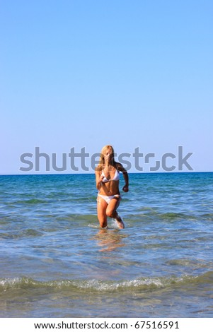 Beautiful young sexy bikini model by the sea  running in the water - stock photo