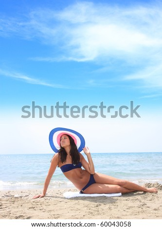 Beautiful young sexy bikini model with hat by the sea - stock photo